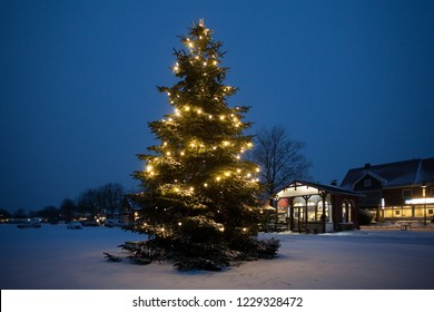Rodenkirchen, Germany - January 05, 2016: enlightened christmas tree on the snowy market square at a scenic dawn