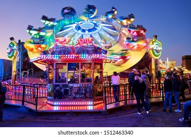 """Rodenkirchen, Germany - September 21, 2019: thrilling high speed carousel """"Flipper"""" colorfully enlightened at dawn during the fair """"Roonkarker Mart"""""""