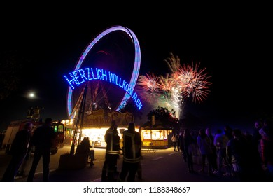 """Rodenkirchen, Germany - September 25, 2018: fireworks behind a moving giant wheel and the welcome sign of the fair """"Roonkarker Mart"""" (the German """"Herzlich Willkommen"""" means """"welcome"""" in English)"""