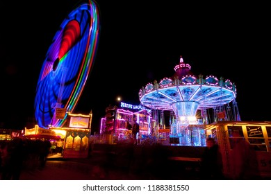 "Rodenkirchen, Germany - September 25, 2018: a traditional chair swing ride next to the high speed carousel ""VMAXX"" in motion on the fair ""Roonkarker Mart"" at night"