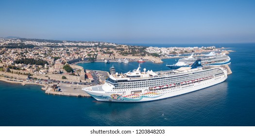 Rodos, Greece - September 24, 2018: Aerial panoramic image of the old port of Rodos, including the Norwegian Spirit cruise ship docked at the old town port and a general view of the old city and bay.