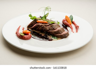 Roe deer fillet with vegetables, purple potato puree and red wine sauce
