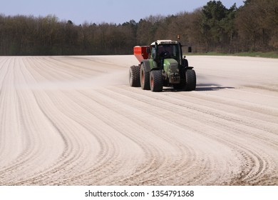 ROERMOND, NETHERLANDS - MARCH 30. 2019: Chalk fertilizer application by tractor with spreader to prepare the field for growing grass lawn