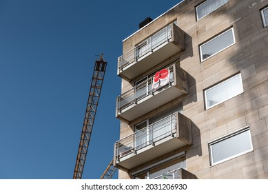 Roeselare, East Flemish Region - Belgium - 07 19 2021: Rectangular facade of an apartment block with a crane and blue sky