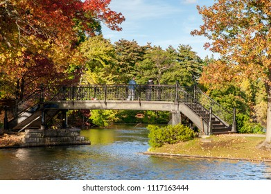 Roger Williams Park, Rhode Island, USA - October 13, 2009: Two men on footbridge overlooking Polo Lake in Roger Williams Park