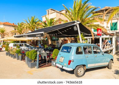 ROGOZNICA PORT, CROATIA - SEP 5, 2017: Classic old car parking in front of traditional restaurant buildings in Rogoznica port, Dalmatia, Croatia.