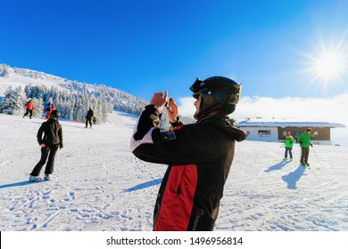Rohrberg, Austria - February 4, 2019: Man taking photos in Zillertal ski resort in Tyrol in Mayrhofen in Austria in winter Alps. People and Ski in Alpine mountains with white snow and blue sky.