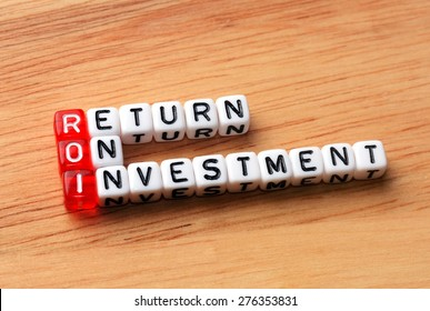 ROI Return On Investment written on dices on wooden  background