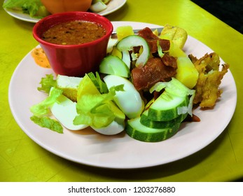 Rojak with fried dough shrimp fritters,tofu,egg,cuttlefish,shredded cucumber and turnip in thick spicy peanut gravy sauce. Popular Street Food made by Indian muslim in Malaysia