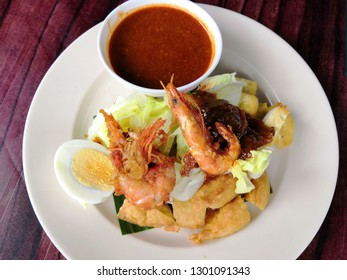 Rojak with fried dough shrimp fritters,tofu,egg,cuttlefish,shredded cucumber and turnip in thick spicy peanut gravy sauce. Popular Street Food made by muslim in Malaysia - Image