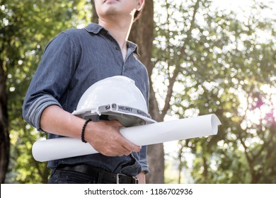 Role of civil engineer holding white safety helmet and blueprint outside, Asian engineer looking and surveying at a construction site