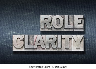 role clarity phrase made from metallic letterpress on dark jeans background