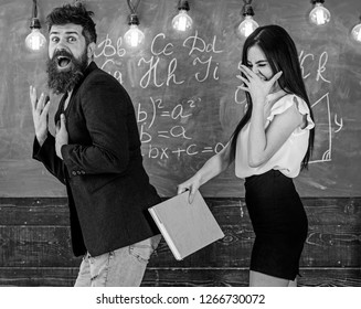Role games concept. Girl on smiling face having fun while punishes teacher. Student lady slapping on teachers buttocks with book. Man with beard punished by sexy student, chalkboard on background.