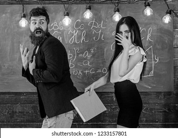 Role games concept. Student lady slapping on teachers buttocks with book. Girl on smiling face having fun while punishes teacher. Man with beard punished by sexy student, chalkboard on background.