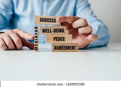 The role of the mediator in maintaining stability in life. Man arranges wooden blocks with inscription PEACE, AGREEMENT supported by a wooden MEDIATOR block. Role of mediation in maintaining order.