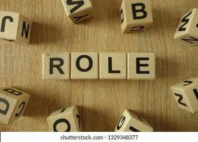 Role word from wooden blocks on desk