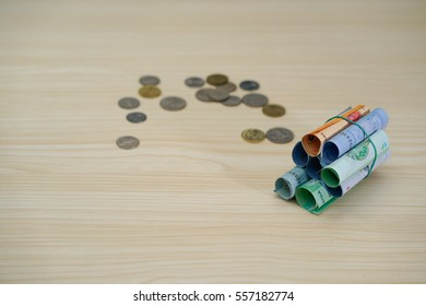 Roles of Bank Note and coins over wooden background