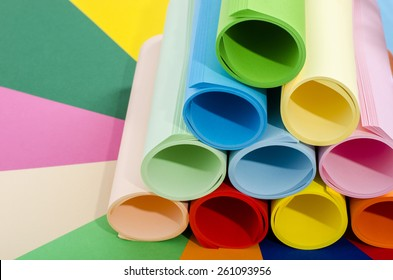 Roles of color paper. Color paper rolled and piled. Stack of paper on multicolor background.