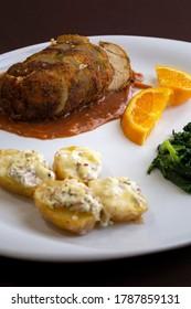 "The ""Rolinho de Frango recheado com Alheira"" is a typical Portuguese dish served with cheese brie potatoes and turnip greens."