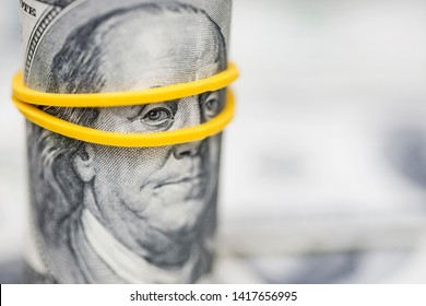 Roll of 100 dollar bills, with an emphasis on the Franklin's eyes with rubberband