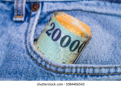 Roll of 20000 Hungarian forint banknotes in a bright pocket of jeans, tied with ellastic rubber band.