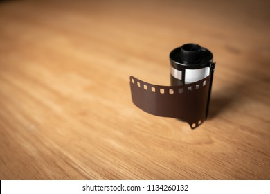 A roll of 35 mm film for cameras on wooden table