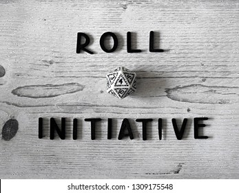 Roll 4 Initiative: D20 polyhedral dice on white wooden background, top view. Before the first round of combat, players roll initiative. Recreational concept for tabletop RPG games