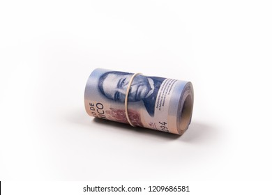 roll of 500 peso mexican bills on white background. with the image of Benito Juarez in sight