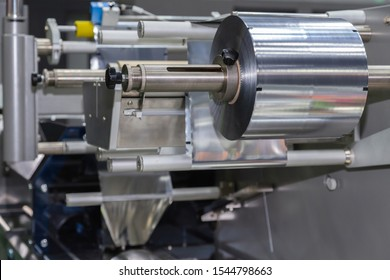roll of aluminum foil for food packaging on the automatic packing machine in food product factory. industrial and technology concept.