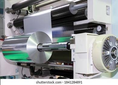 Rolle von Aluminiumfolie für Lebensmittelverpackungen auf automatischer Verpackungsmaschine in Lebensmittelfabrik. Industrie- und Technologiekonzept.