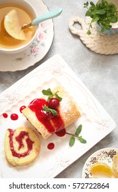 roll biscuit with berry fruit jam and cherries, mint on a white plate