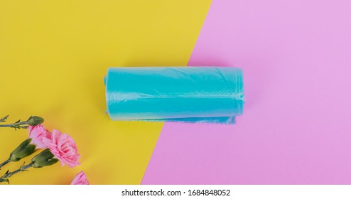 Roll of blue biodegradable trash bags. On a yellow-pink background. Selective focus. Spring theme.  Ecology.