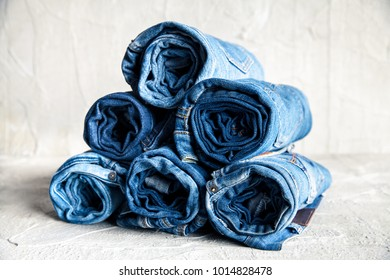 roll blue denim jeans on gray background