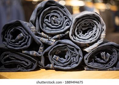 Roll blue denim jeans in a shop. Jeans texture closeup.