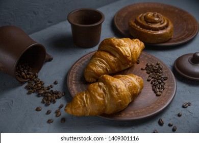 Roll with cinnamon and croissant on a gray background and a cup of coffee with a chocolate bar. coffee bean frame. classic breakfast on concrete background