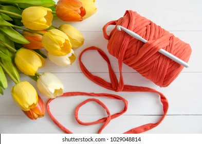 Roll of cotton yarn and a crochet hook with a bouquet of orange and yellow tulips on white wooden background. The concept of crochet, hobby, needlework, self-realization, creativity