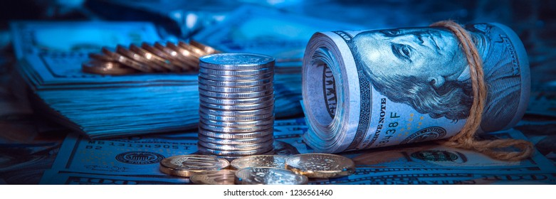 A roll of dollars with coins on the background of scattered one hundred dollar bills in blue light.
