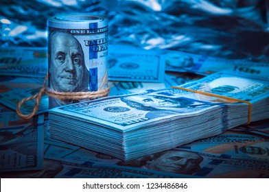 A roll of dollars with a pack of dollars against a background of scattered hundred dollar bills in blue light.