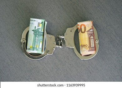 roll Euro money bills (banknotes) of 100 and 50 in handcuffs. Euro bills with handcuffs. Handcuffs and money on table. Financial crime, dirty money and corruption concept. Tax offense concept.