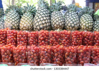Roll of fresh pineapples and red tomatoes ready for sell at market.