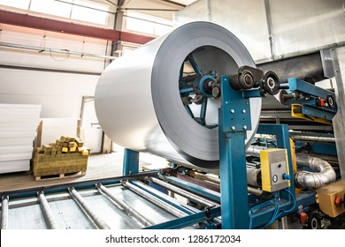 Roll of galvanized steel sheet at conveyor line machine equipment, ironworks and metalwork manufacturing factory production, close up