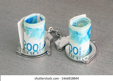 roll Israeli money bills of 200 shekel in handcuffs isolated on gray background. Shekel banknotes with handcuffs. Handcuffs and money on table. Financial crime, dirty money and corruption concept.