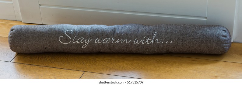 A roll with letters keeping warm inside the house by protecting from air draft and saving heating costs in the winter time.