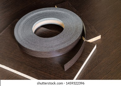 Roll melamine edge for finishing of furniture. Edging tape lying on laminated chipboard sheets wenge color.