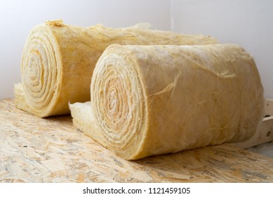 roll of mineral wool lying on the wooden floor
