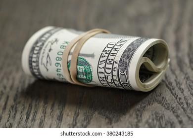 roll hundred dollar bills on wooden stock photo edit now 266813255