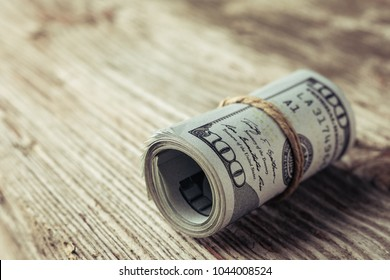 Roll of One Hundred Dollars bill on a wooden table. Cash Money American Dollars. Close-up view of stack of US dollars.