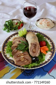 Roll of peritoneum with garlic and spices on a plate decorated with greens. The upper projection.Uzbek cuisine.