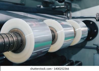 Rolle von Plastikverpackungsfolie auf der automatischen Verpackungsmaschine in der Lebensmittelfabrik. Industrie- und Technologiekonzept. Vintage Foto und Film Stil.