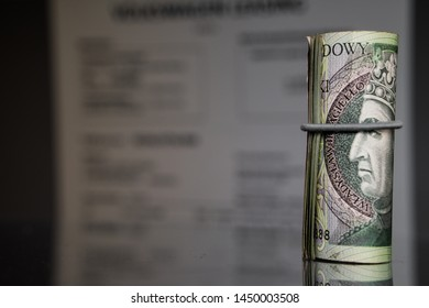 Roll of Polish Zloty banknotes (PLN) - Closeup on 100 PLN banknote roll. Blurred invoice in background. Best for tax, financial topics